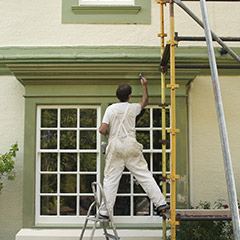 Man on scaffold painting exterior of home