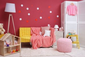 child's room with a red wall and a couch