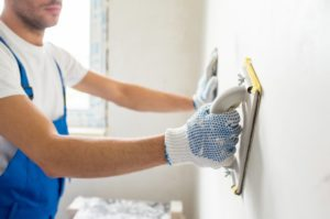 a paint contractor preparing a wall